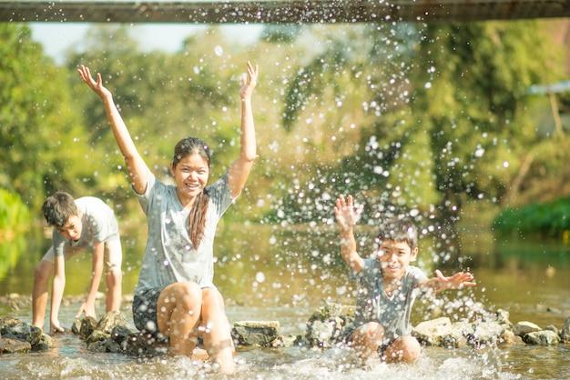 Familie die bij waterval in het bos samen gelukkige reist