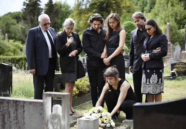 Familie die bloemen op het graf legt
