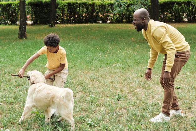 Familie die de hond buiten traint