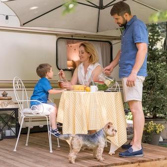 Familie die de lunch buiten een caravan neemt