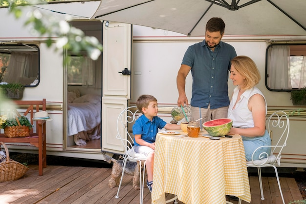 Familie die de lunch naast een caravan neemt