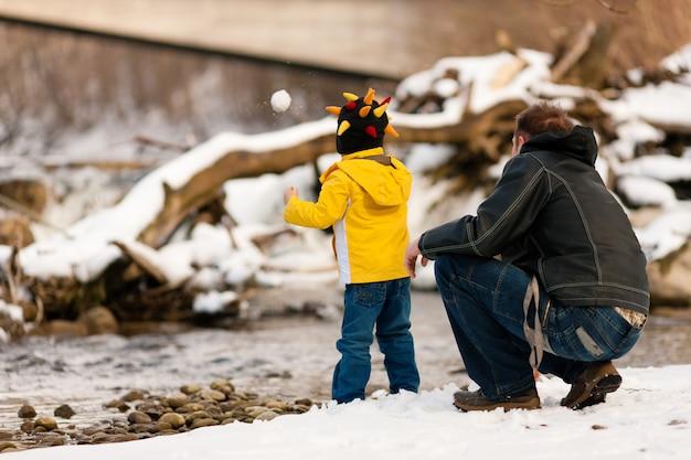 Familie die de wintergang heeft bij rivier