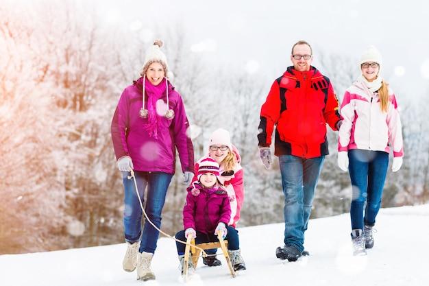 Familie die de wintergang in sneeuw met slee heeft