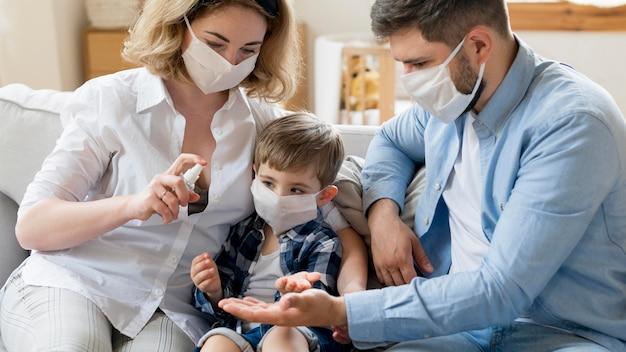 Familie die desinfectiemiddel gebruikt en medische maskers draagt