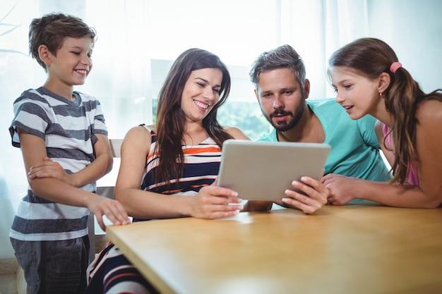 Familie die digitale tablet gebruikt terwijl het zitten bij lijst