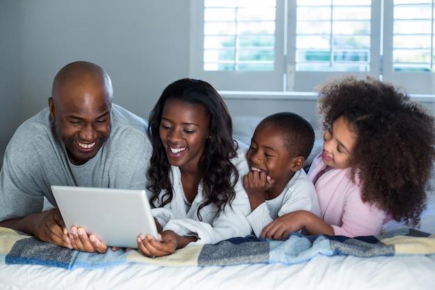 Familie die digitale tablet op bed gebruiken