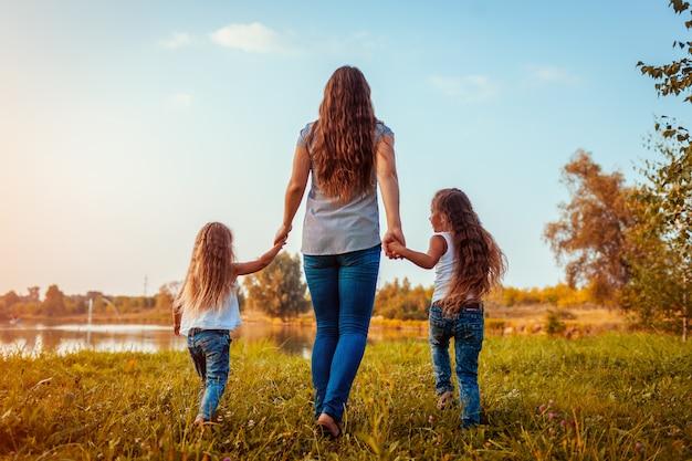 Familie die door de zomerrivier bij zonsondergang loopt. moeder en haar dochters plezier buitenshuis.