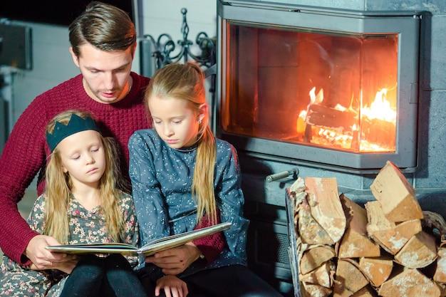 Familie die een boek samen leest dichtbij open haard op kerstavond