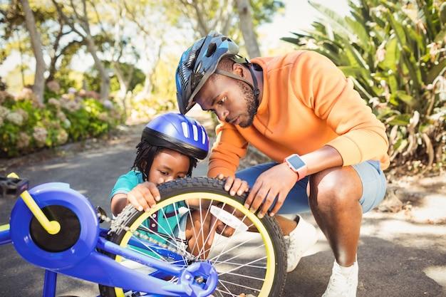 Familie die een fiets herstelt