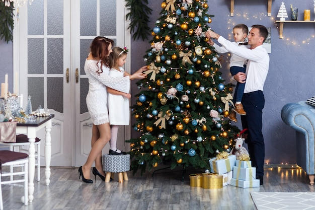 Familie die een kerstboom thuis verfraait