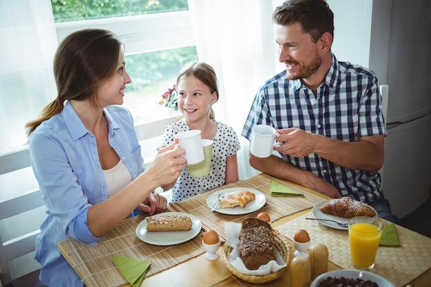 Familie die een kop van koffie roostert terwijl ontbijt