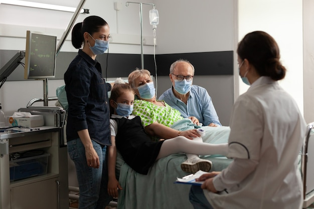 Familie die een oudere oudere vrouw bezoekt terwijl ze een beschermend gezichtsmasker draagt