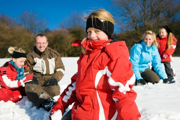 Familie die een sneeuwballengevecht heeft