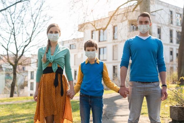 Familie die een wandeling in de zon heeft tijdens coronavirusnoodsituatie