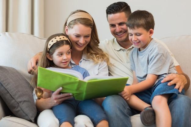 Familie die fotoalbum op bank bekijkt