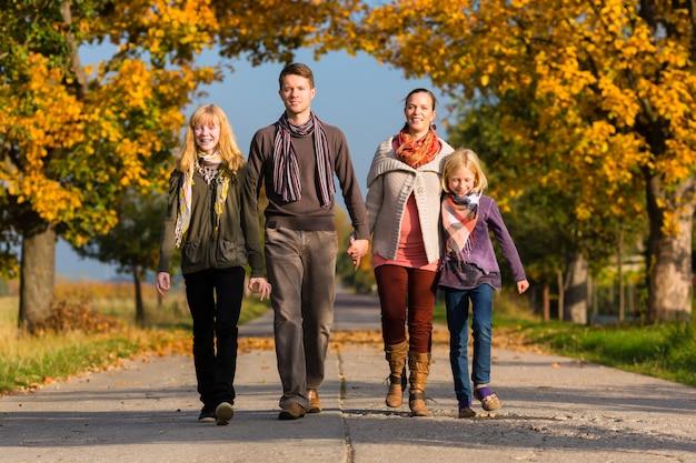 Familie die gang voor kleurrijke bomen in de herfst hebben