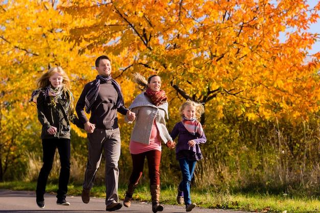 Familie die gang voor kleurrijke bomen in de herfst heeft