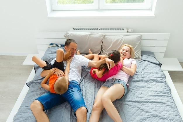 Familie die grappig hoofdkussengevecht op bed heeft. ouders brengen vrije tijd door met hun dochters.