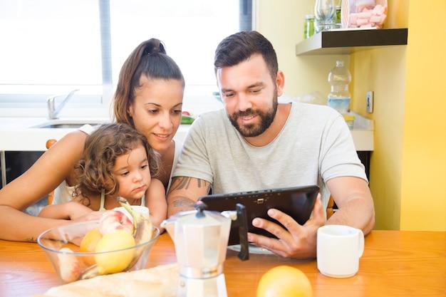 Familie die het digitale tabletscherm tijdens ontbijt bekijkt