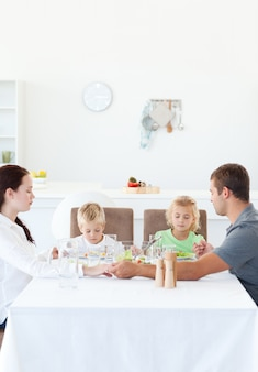 Familie die hun handen houdt terwijl het bidden alvorens een salade te eten