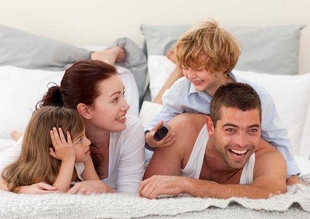 Familie die in bed en zoon ligt die een afstandsbediening gebruiken