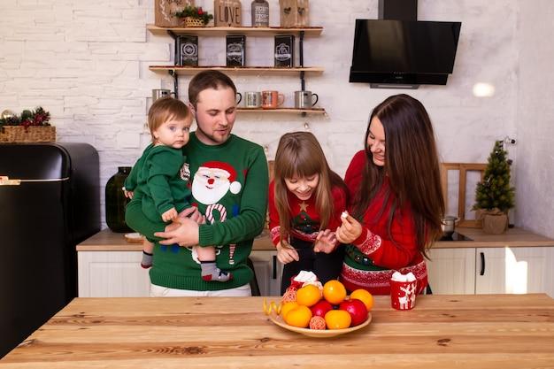 Familie die in keuken thuis op kerstmis wacht. vrolijk kerstfeest en een gelukkig nieuwjaar