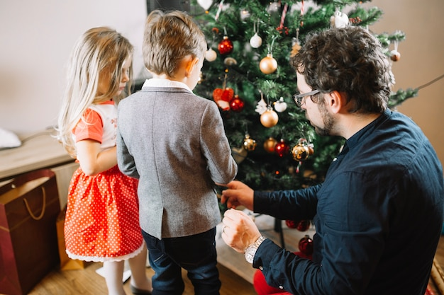 Familie die kerstmisboom bekijkt