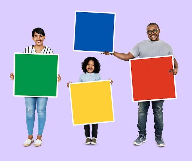 Familie die kleurrijke vierkante raad houdt