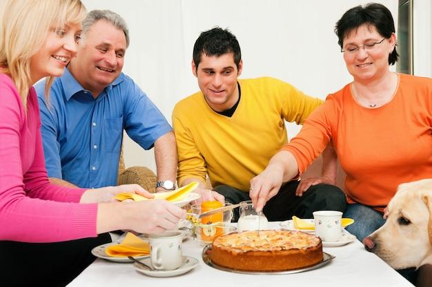 Familie die koffie en cake heeft samen