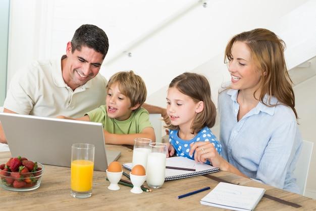 Familie die laptop met behulp van terwijl het ontbijten