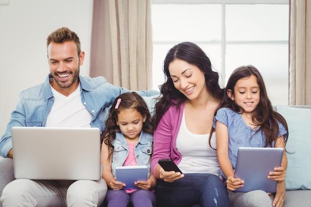 Familie die moderne technologieën gebruikt terwijl het zitten op bank