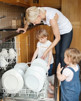 Familie die naast de afwasmachine staat