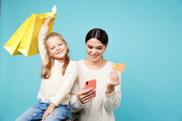 Familie die online concept winkelt. moeder met dochter.