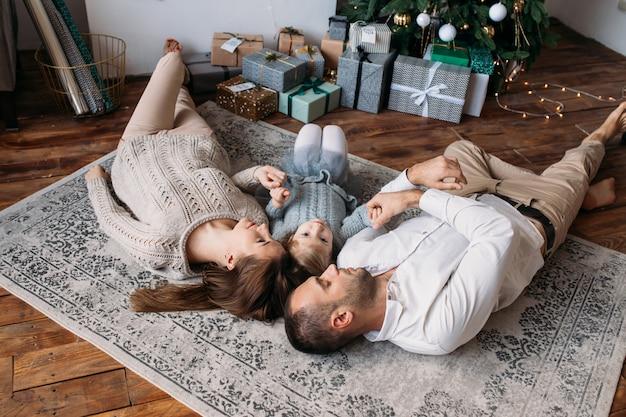 Familie die op de vloer thuis ligt. geschenkdozen en kerstboom
