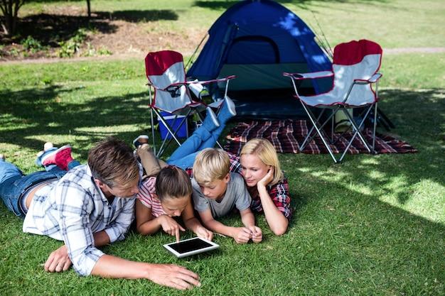 Familie die op gras ligt en digitale tablet gebruikt