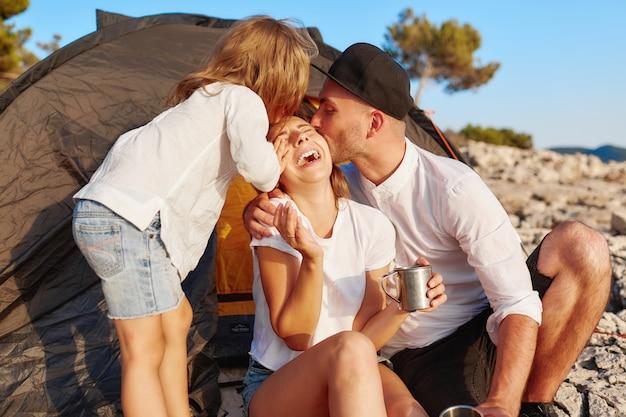 Familie die op rotsachtige kust, meisje rust die hand uitdeelt om omhelzemoeder te geven.