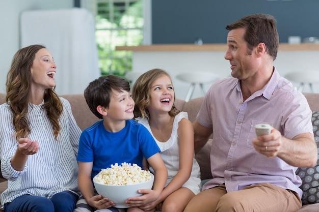 Familie die op tv letten en thuis popcorn in woonkamer eten