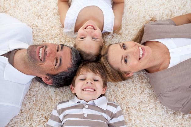 Familie die op vloer met hoofden samen ligt