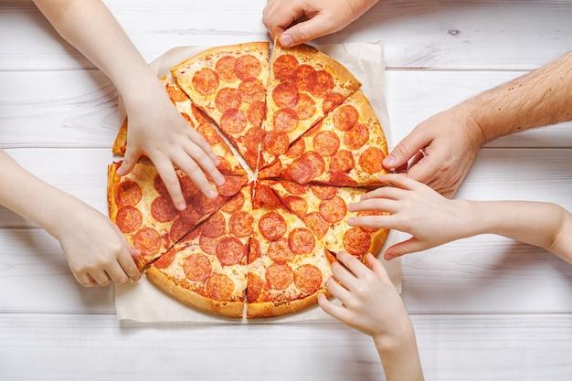 Familie die peperoni pizza eet. kinderen en vaders houden een plak pizza.