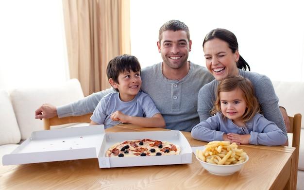 Familie die pizza en gebraden gerechten op een bank eet