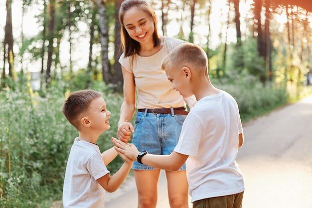 Familie die plezier heeft tijdens het wandelen in het zomerpark en lacht, kleine jongen geeft een high five aan zijn oudere broer, gelukkige kinderen die in de buurt van hun lachende moeder staan.