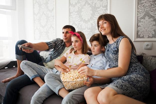 Familie die popcorn thuis eet tijdens het letten op televisie