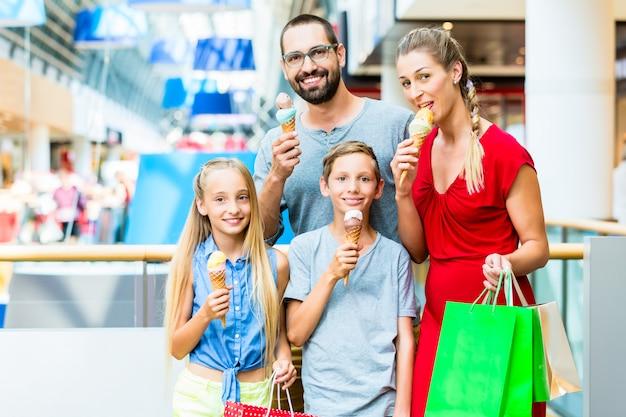 Familie die roomijs in winkelcomplex met zakken eet