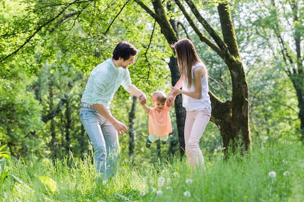 Familie die samen in de zomer hand in hand loopt en de kleine jongen laat vliegen
