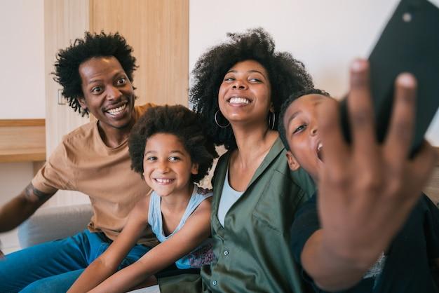 Familie die selfie samen met telefoon thuis nemen.