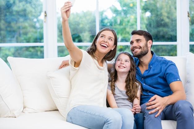 Familie die selfies klikt terwijl het zitten op bank