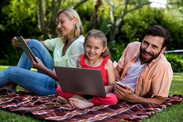 Familie die technologieën gebruikt die in werf ontspannen