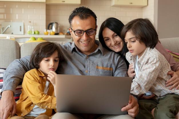 Familie die thuis samen op laptop kijkt