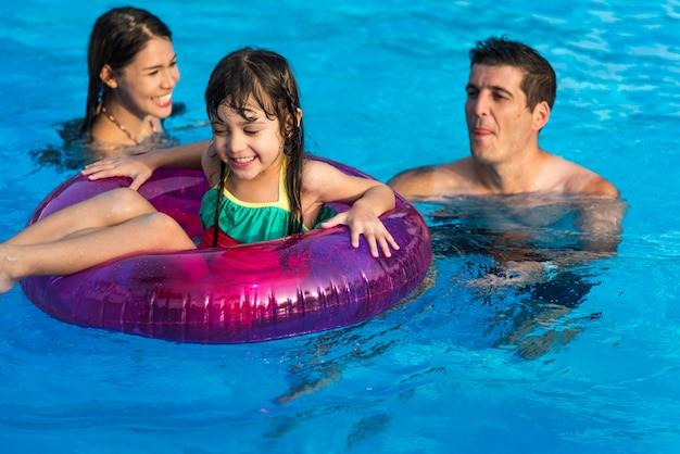 Familie die van een aardige dag bij de pool geniet