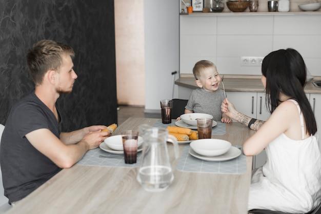 Familie die van het ontbijt in de keuken geniet